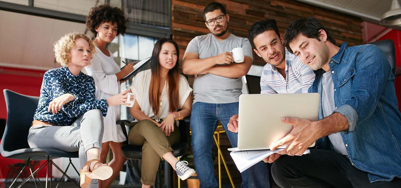 three women and three men agile team meeting around a laptop